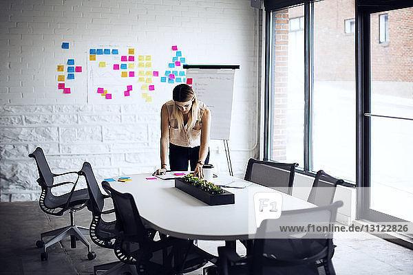 Seriöse Geschäftsfrau  die am Tisch im Kreativbüro arbeitet