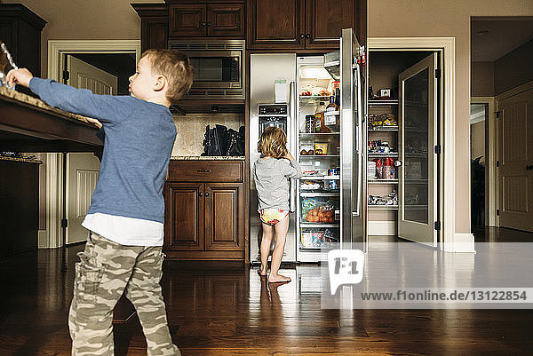 Boy standing by refrigerator with brother at home