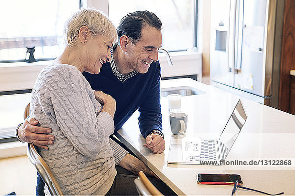 Smiling senior couple looking at laptop computer while sitting by table