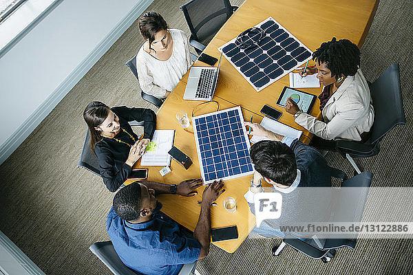 Draufsicht auf Geschäftsleute  die während des Treffens über Solarpanel-Modelle diskutieren