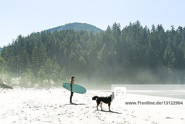 Woman holding surfboard with dog standing at cannon beach