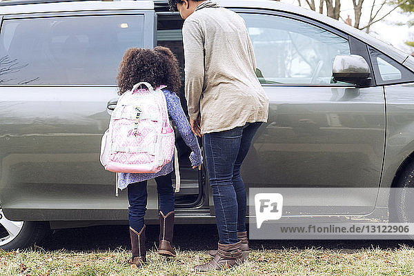 Mother and daughter standing by car