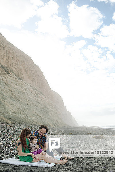 Family relaxing at beach by mountain against cloudy sky