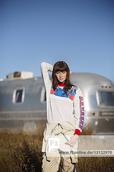 Portrait of young woman standing on field with trailer home in background