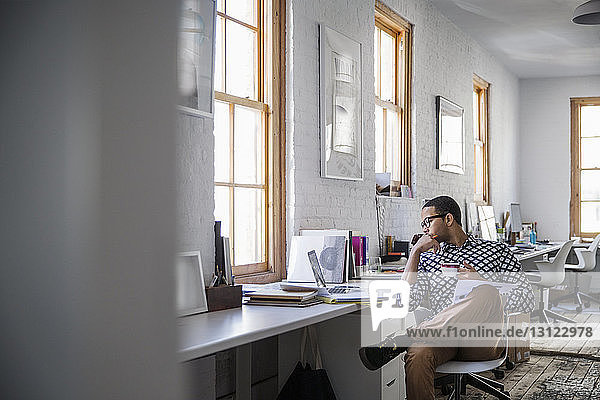 Businessman looking at laptop while working in creative office