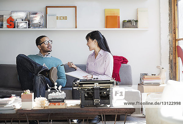 Businesswoman discussing with male colleague in creative office