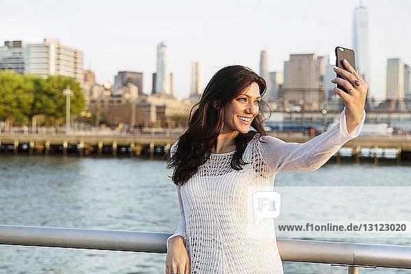 Glückliche Frau  die sich beim Stehen auf der Promenade mit dem Eine-Welt-Handels-Zentrum im Hintergrund egoistisch verhält