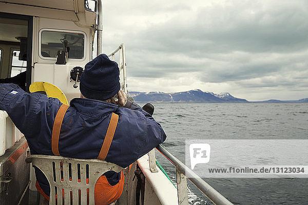 Rückansicht eines Fischers  der in einem Fischerboot sitzt