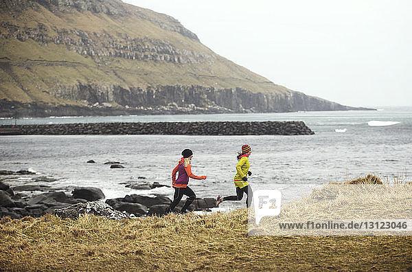 Freundinnen joggen auf dem Feld gegen das Meer