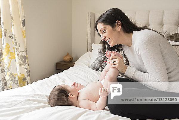 Lächelnde Mutter spielt mit hemdlosem Sohn  der zu Hause auf dem Bett liegt
