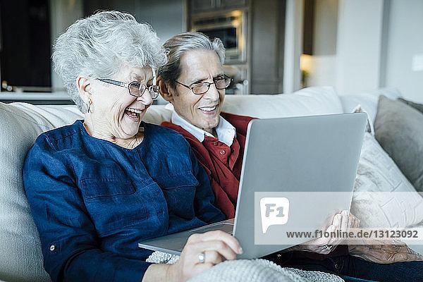 Glückliches älteres Ehepaar bei Videokonferenzen auf dem Sofa sitzend per Laptop