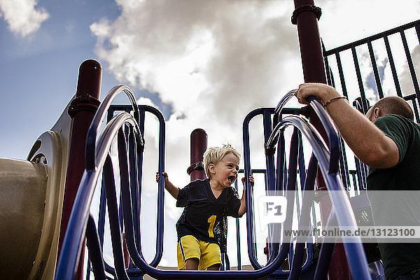 Niedrigwinkelansicht eines Jungen  der den Vater anschreit  während er auf einer Rutsche auf dem Spielplatz steht