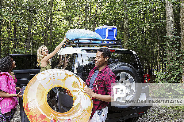 Friends unloading inner tubes from car roof in forest