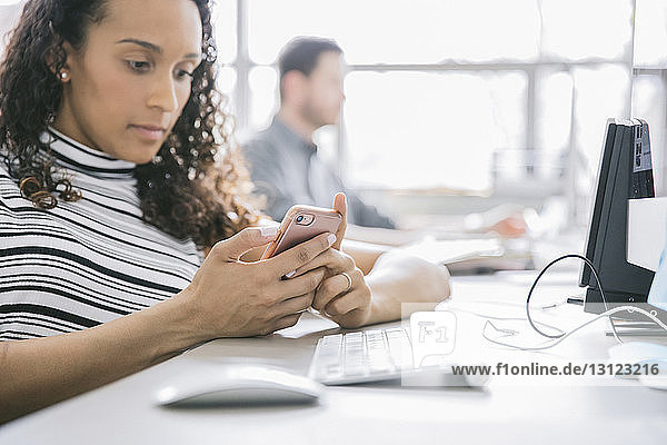 Businesswoman using mobile phone while male colleague in background