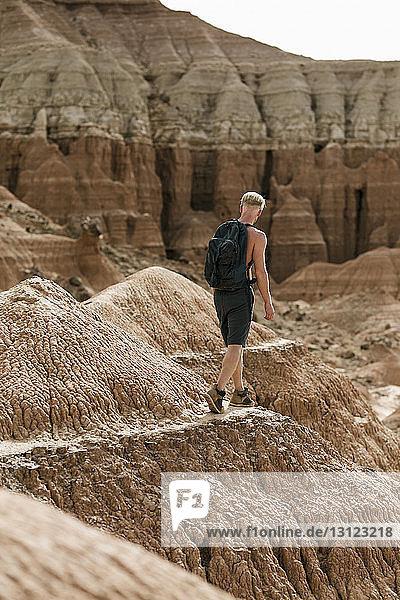 Wanderer in voller Länge mit Rucksack gegen Felsformationen in der Wüste