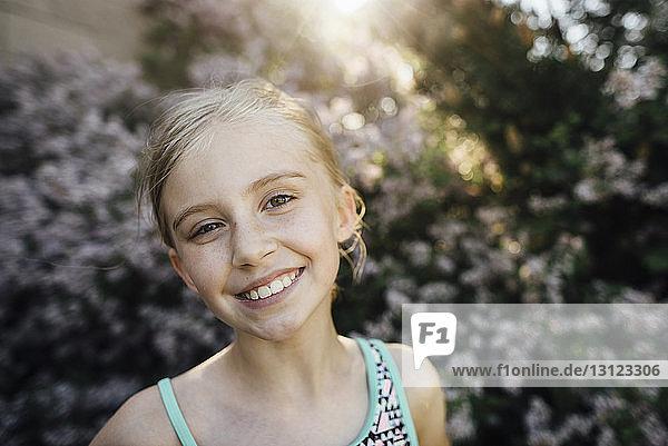 Porträt eines lächelnden Mädchens  das im Hinterhof vor Pflanzen steht