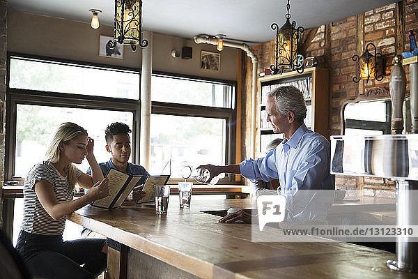 Besitzer serviert Kunden Getränke an der Bartheke im Cafe