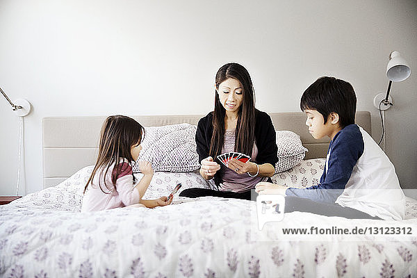 Family playing cards on bed at home