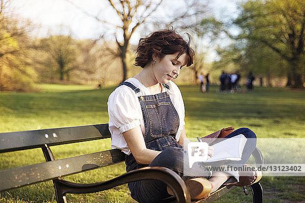 Frau  die im Schneidersitz auf einer Parkbank sitzend im Schneidersitz schreibt