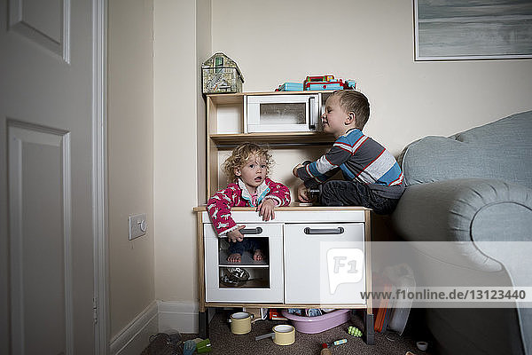Siblings playing on cabinet by sofa at home