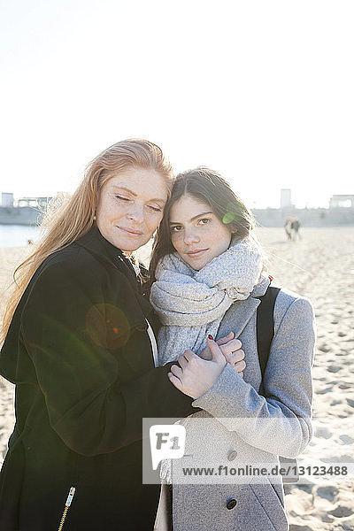 Porträt einer Tochter mit Mutter am Strand während eines sonnigen Tages