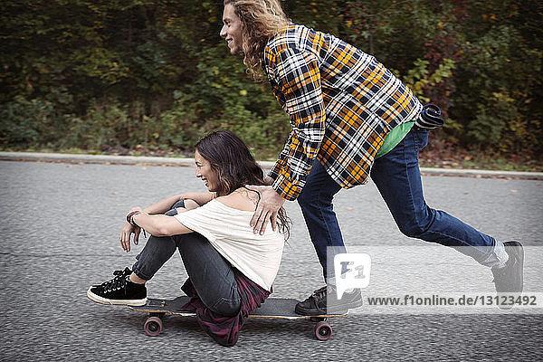 Mann schiebt Frau auf Skateboard sitzend auf Straße