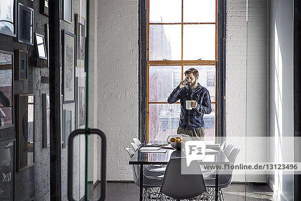 Geschäftsmann telefoniert  während er im Kreativbüro eine Kaffeetasse hält