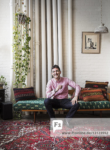 Full length portrait of smiling man sitting on chaise longue at home