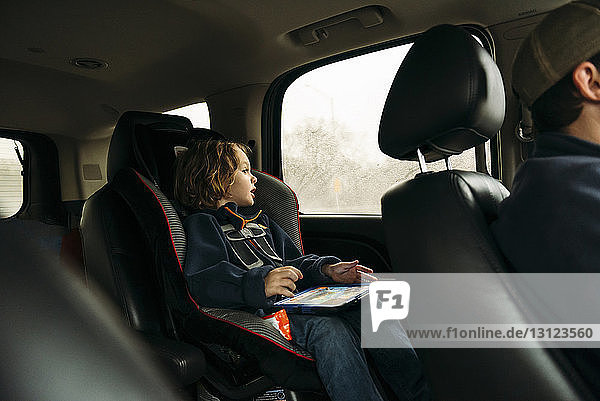 Boy looking through window while sitting in car