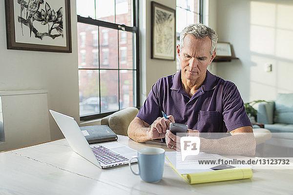 Ernsthaft reifer Mann  der zu Hause ein Smartphone mit Laptop auf dem Tisch benutzt