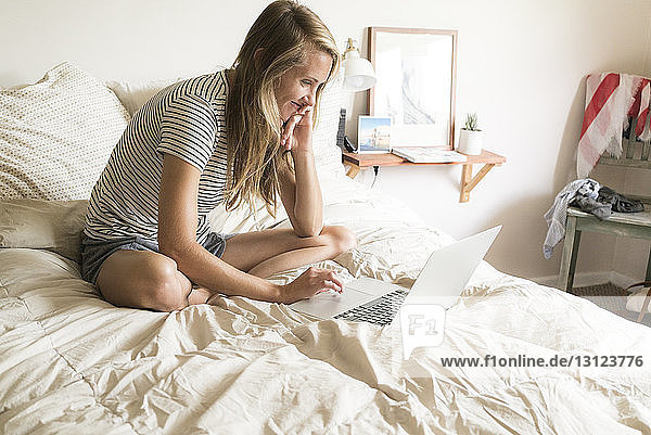 Smiling woman using laptop computer while sitting on bed