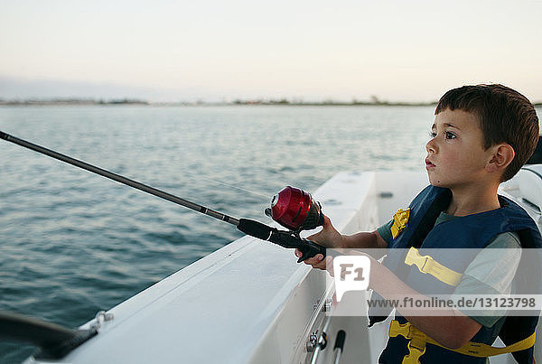 Boy fishing on boat against sky