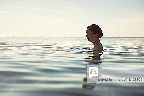 Profilansicht einer nachdenklichen Frau im Meer gegen den Himmel
