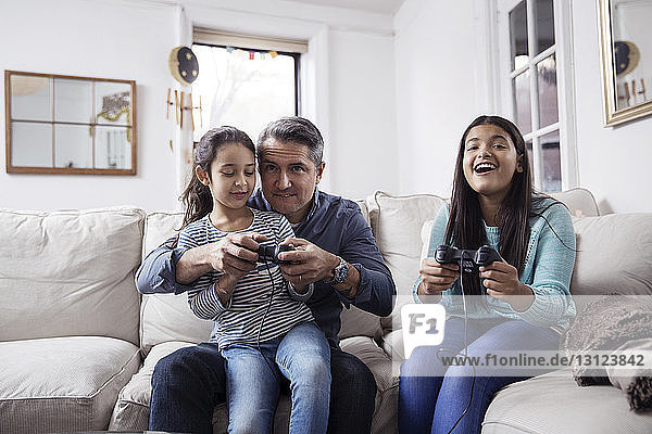 Girls with father playing video game while sitting on sofa at home