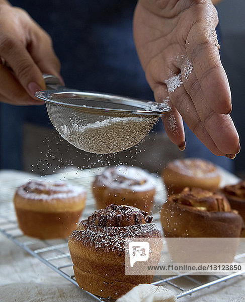 Cropped hands of woman sieving icing sugar on cinnamon buns