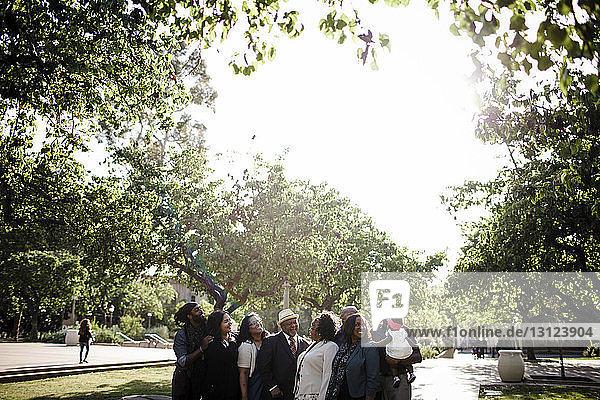 Glückliche Familie redet  während sie auf dem Fußweg gegen den Himmel im Park steht