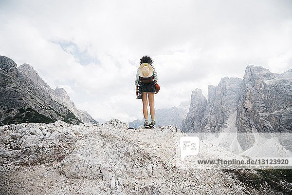 Rear view of female hiker standing on rock against cloudy sky