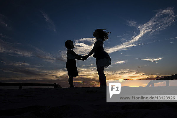 Silhouette sisters holding hands while standing on field against sky during sunset