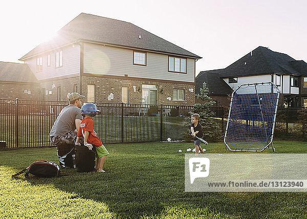Family playing baseball at backyard on sunny day