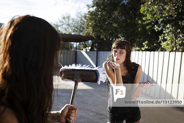 Playful woman blowing soap sud while friend holding broom