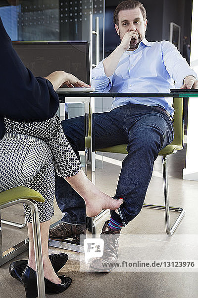 Low section of businesswoman playing footsie with male colleague at conference table