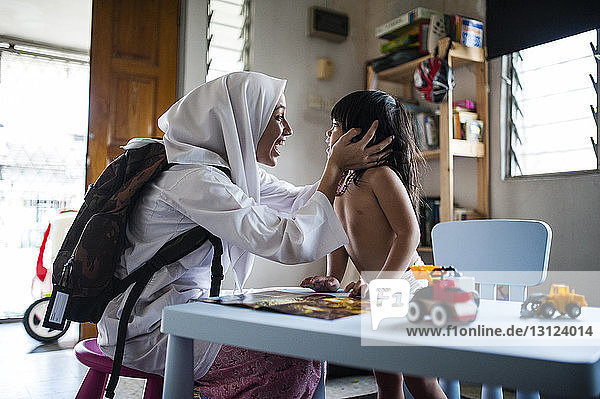 Fröhliches Teenager-Mädchen schaut dem Bruder zu  der zu Hause mit Spielzeug spielt