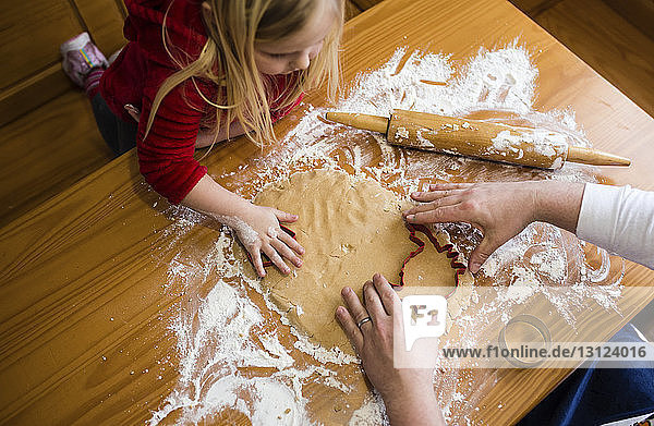 High angle view of girl looking at father making cookies on wooden table at home