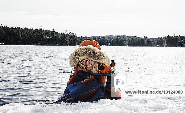 Fröhliche Frau trägt Pelzmantel  während sie im Winter im Algonquin-Provinzpark in eine Decke gegen den See gewickelt wird