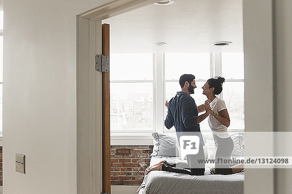 Romantic couple holding hands while kneeling on bed seen through doorway at home
