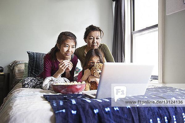 Familie schaut Film im Laptop im Bett
