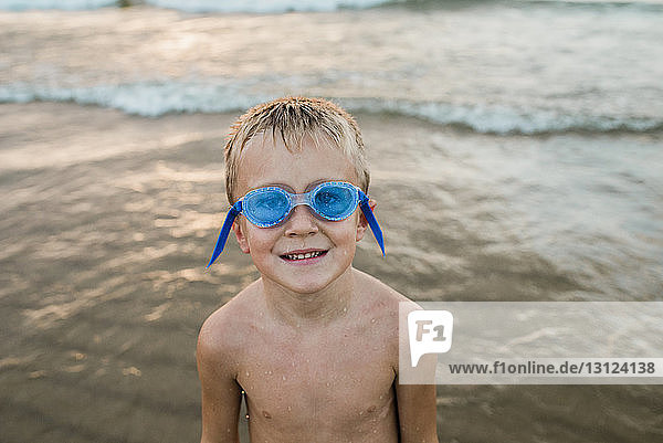 Portrait of shirtless boy wearing swimming goggles while standing on shore at beach