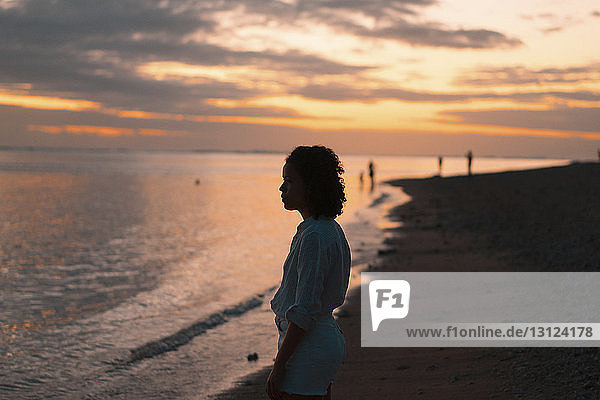 Side view of woman standing at beach against cloudy sky during sunset