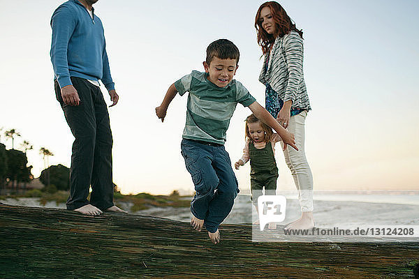 Family looking at boy jumping on rock while standing against clear sky