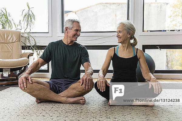 Lächelndes Paar  das sich beim Sport zu Hause von Angesicht zu Angesicht gegenübersteht